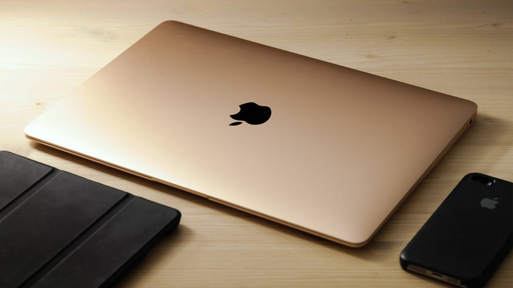 A photo of a MacBook and an iPhone.