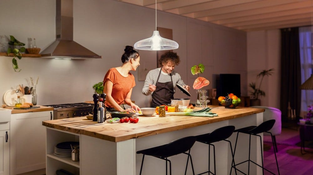 Two people in a kitchen standing beneath a very bright light.