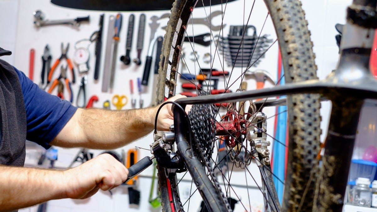 A bike mechanic working on a mountain bike with tools in the background