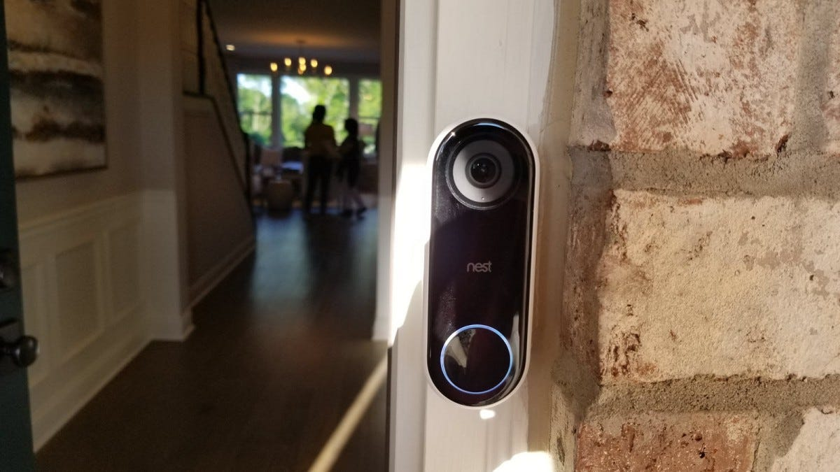 A Nest Hello doorbell mounted to door trim.