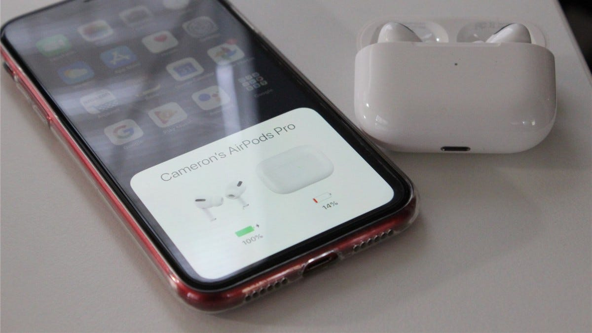 AirPods Pro open next to an iPhone XR showing the battery status screen