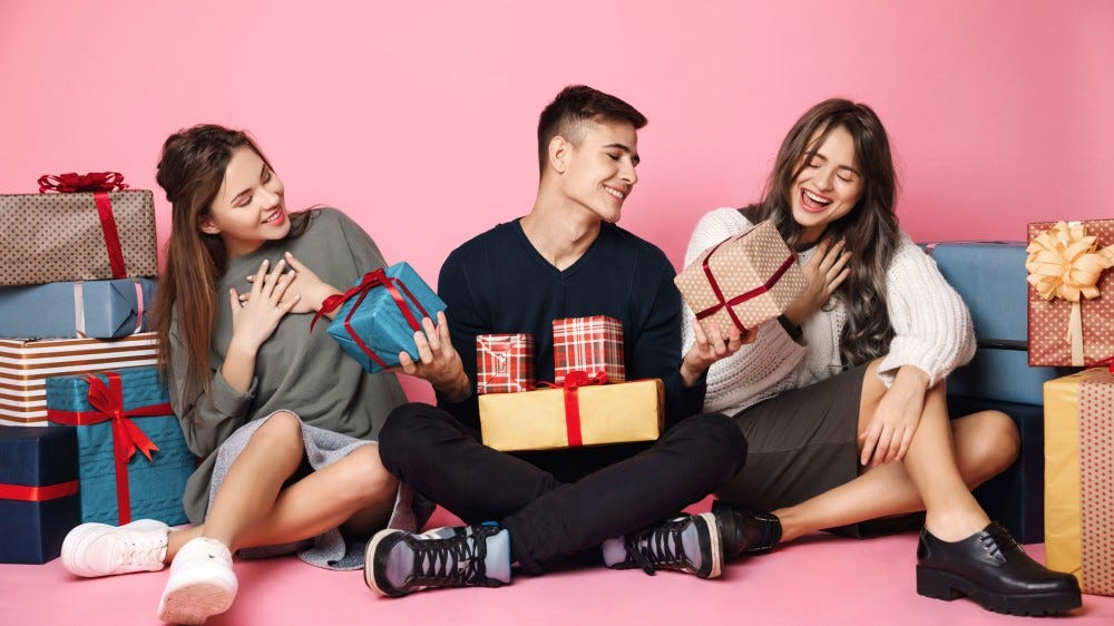 Group of young friends opening gifts on a pink background