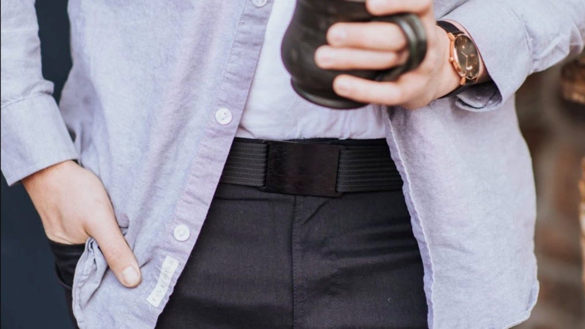 A man's hand holding a coffee mug and wearing a black Grip6 belt over dark slacks.