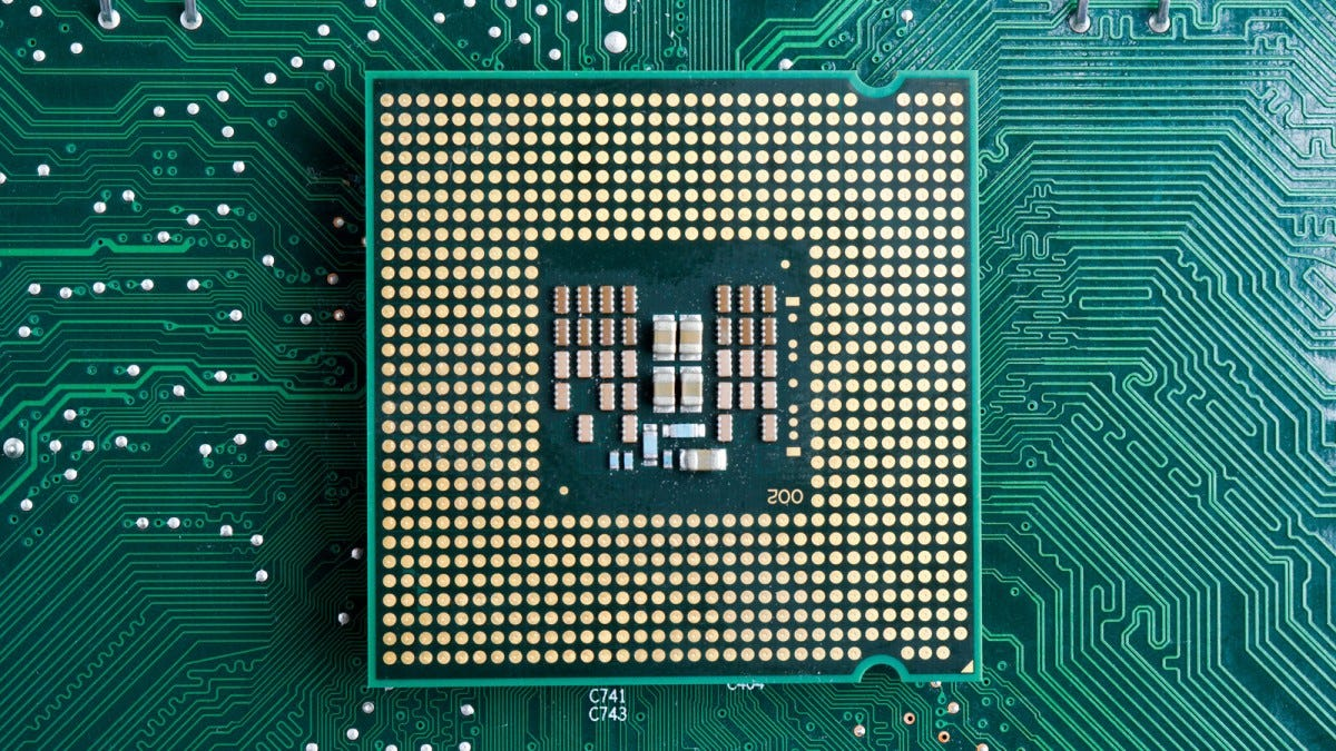 The underside of a processor over a motherboard.