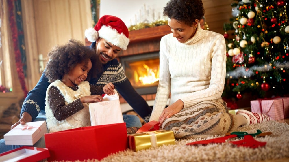 Parents looking at their child opening Christmas presents in front of fireplace and Christmas tree