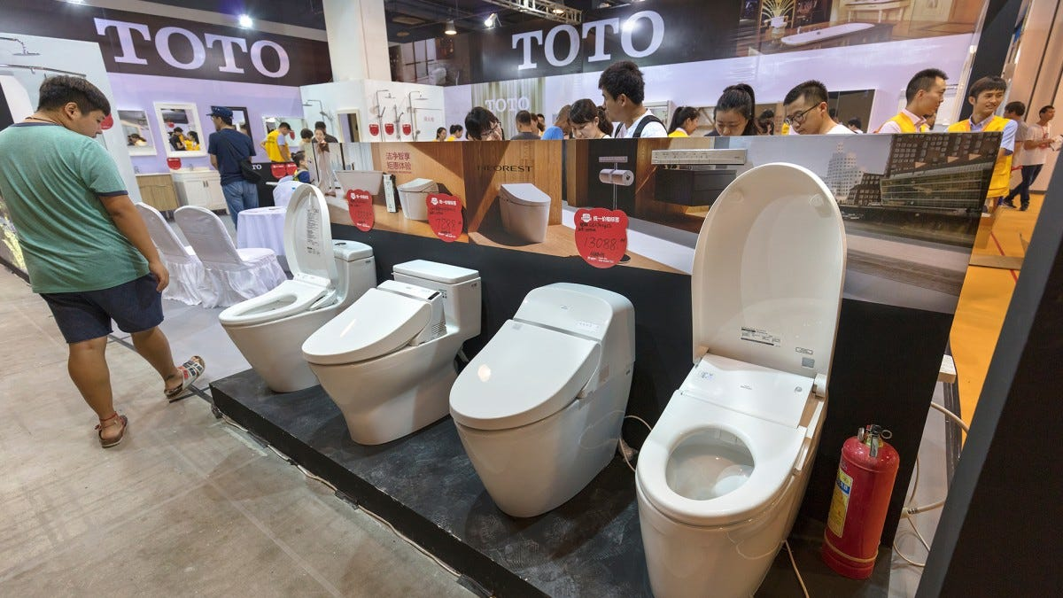 A group of people looking at TOTO smart toilets.