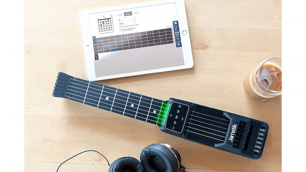 Jamstik Guitar Trainer on table with tablet and coffee mug and headphones