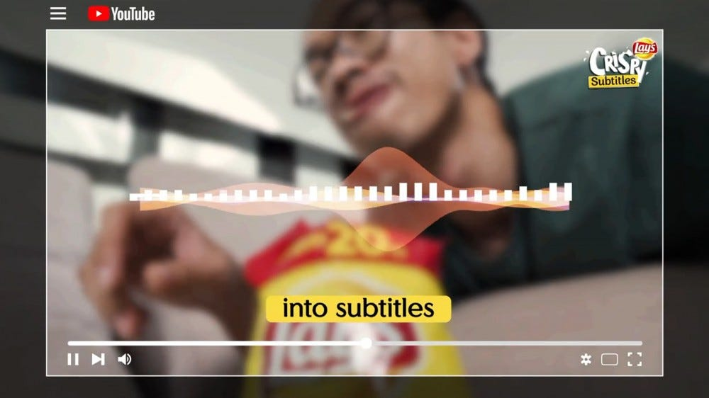 A man eating Lay's chips while watching YouTube.
