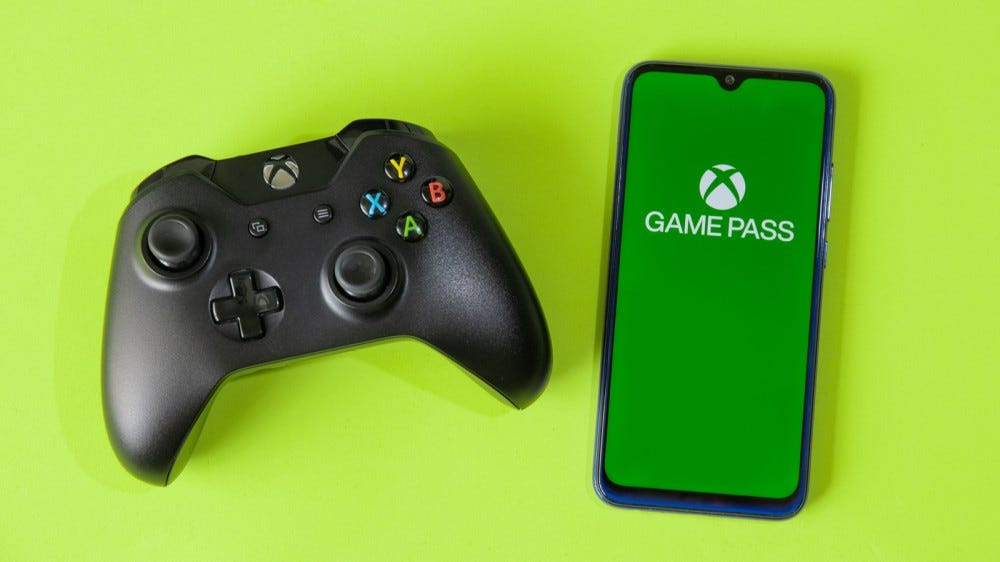 Xbox Game Pass app on smartphone next to an Xbox One controller