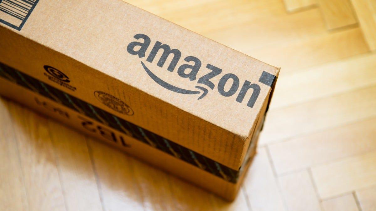 An Amazon box sitting on a hardwood floor.