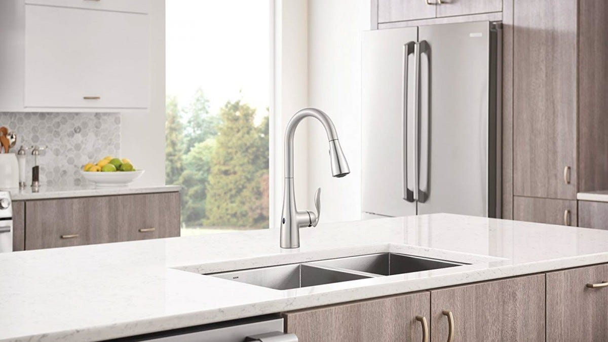 A Moen Motionsense smart faucet, installed in a kitchen island with sink.