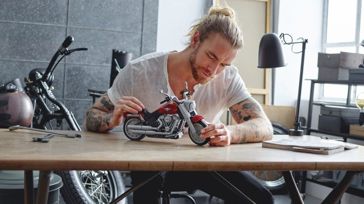 A man at a desk looking at a LEGO motorcycle.