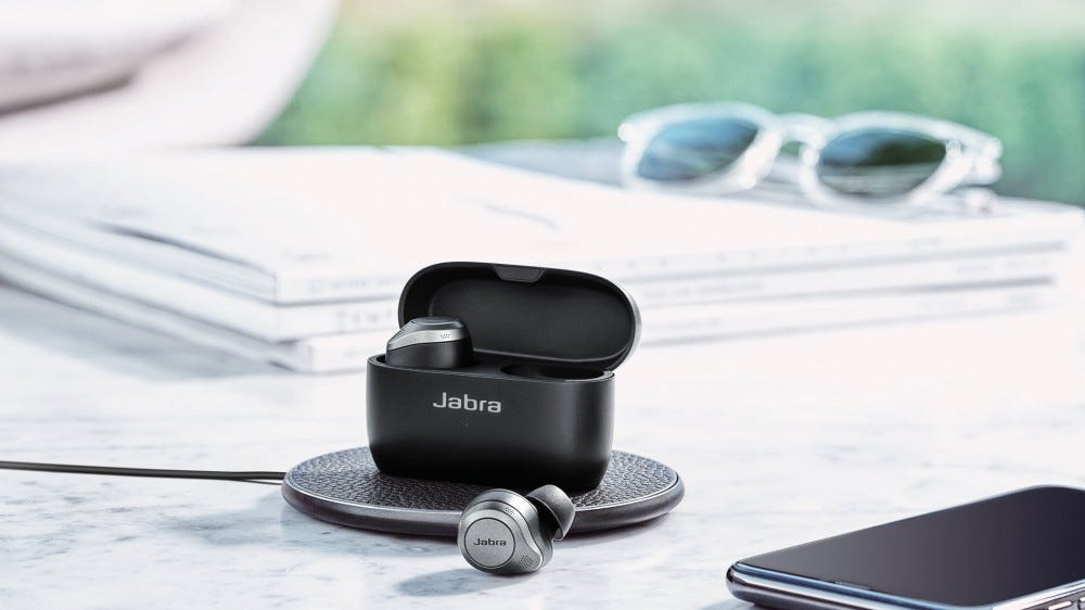 A set of Jabra Elite 85T earbuds in a case on a wireless charger.