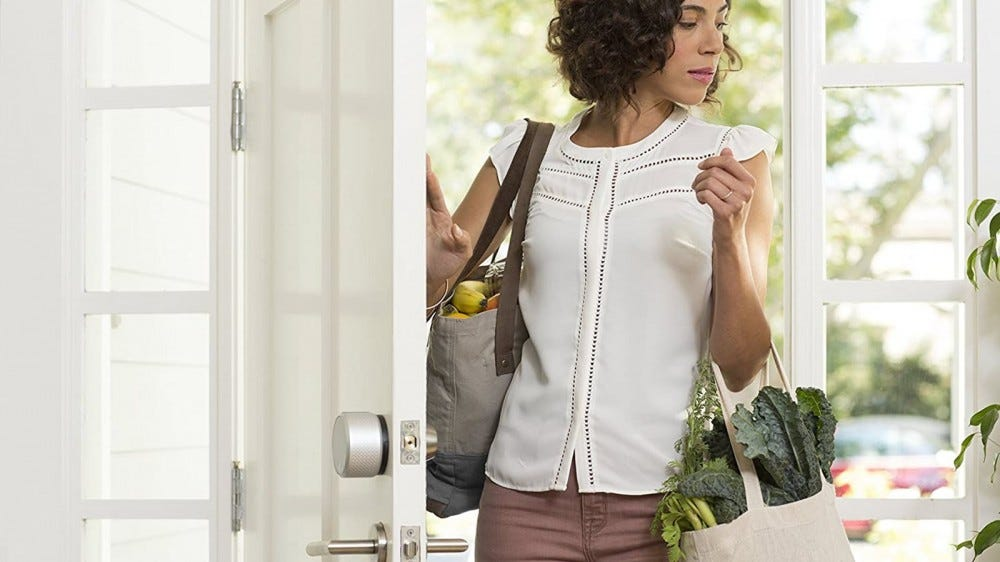 A woman entering a home with an August smart lock attached to the door.