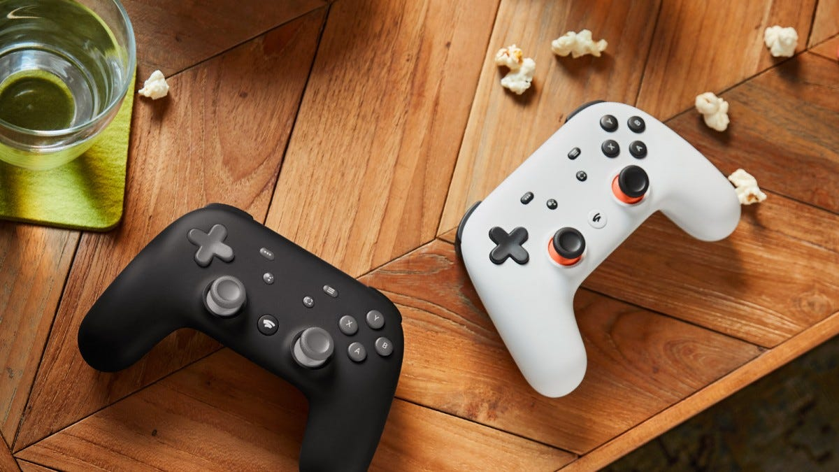 Two Stadia controllers, one black and one white, on a wooden coffee table.