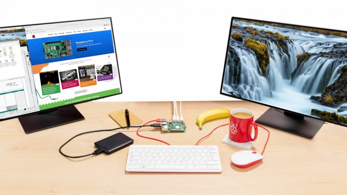 The Pi 4 connected to a keyboard, mouse, and two monitors, and being used as a desktop computer.
