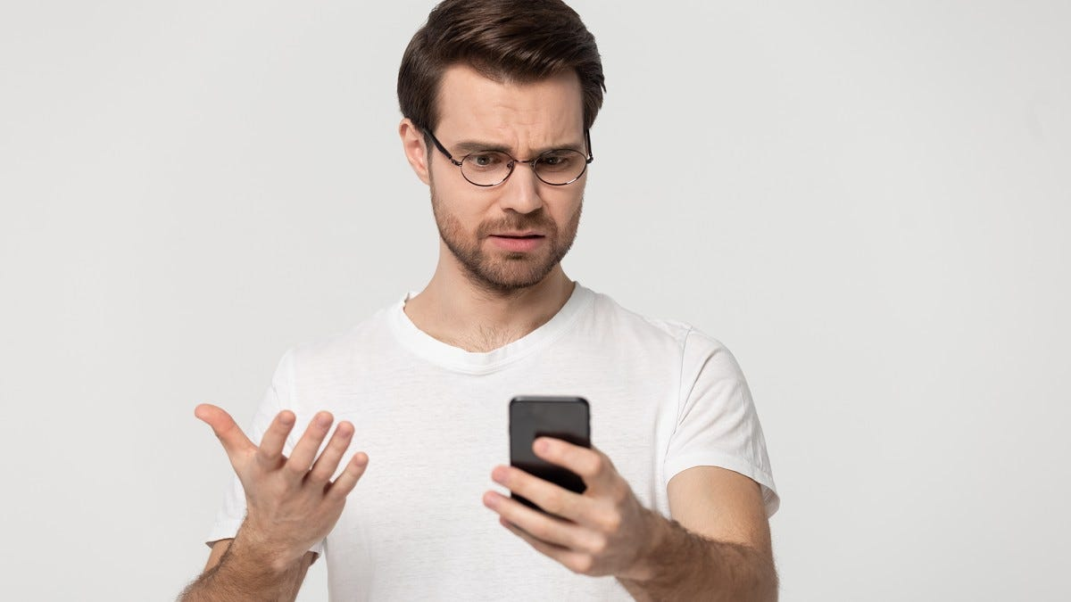 A man looks at his phone with the palpable feeling of disgust, frustration, and shame.