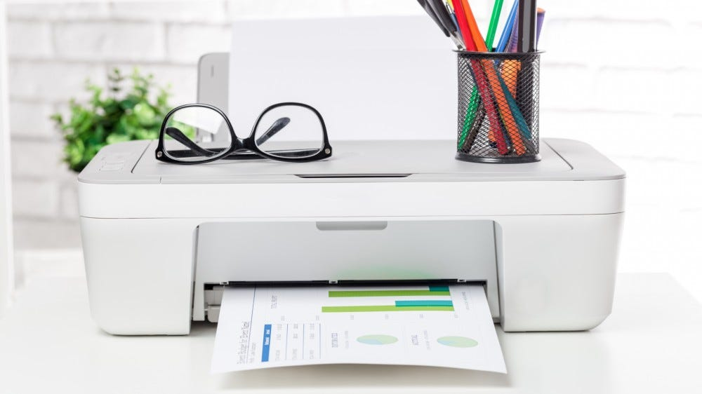 A printer on a desk with papers, glasses, and writing utensils