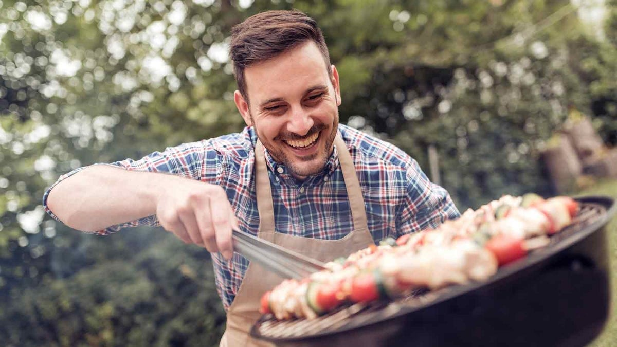 Happy man grilling meat on a back yard barbecue