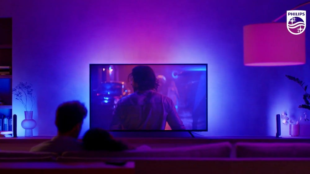 Philips Hue Play Gradient Lightstrip reflects colors on the wall behind TV, with a couple sitting on the couch in the foreground looking at it