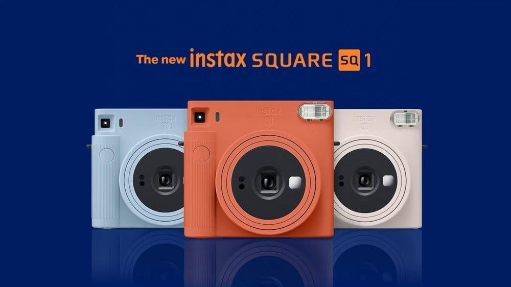 An illustration of the Instax Square SQ1 in blue, red, and chalk white.