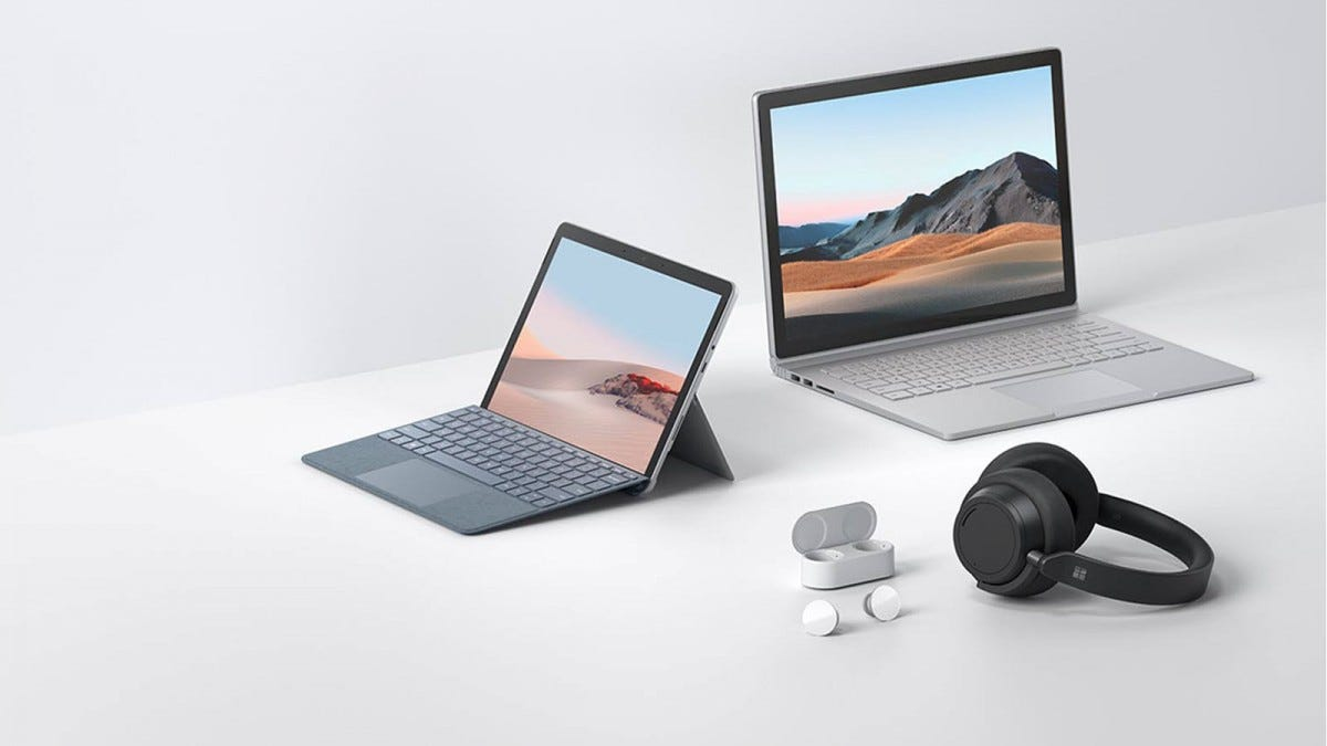 A Surface Book 3, Surface Go 2, set of Surface Headphones 2, and Surface Buds on a white counter.