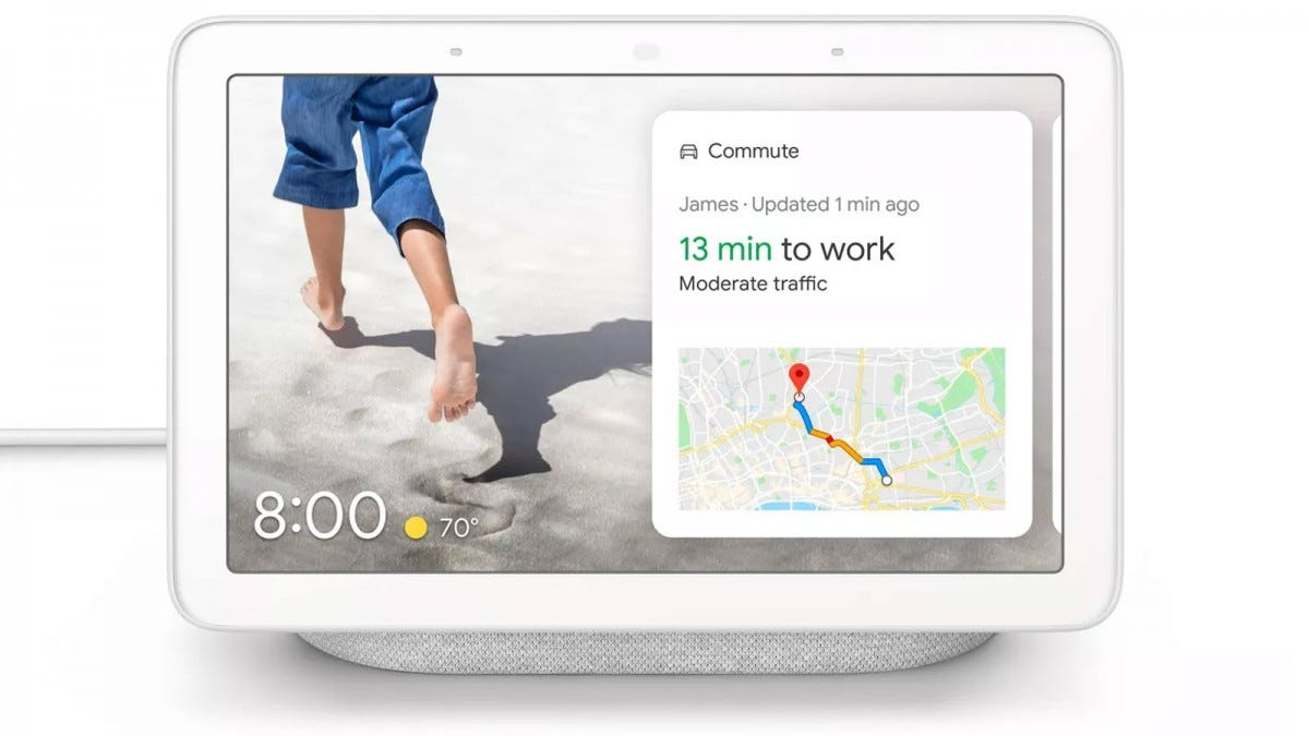 A white Google Nest Hub displaying a photo of a person walking on the beach.