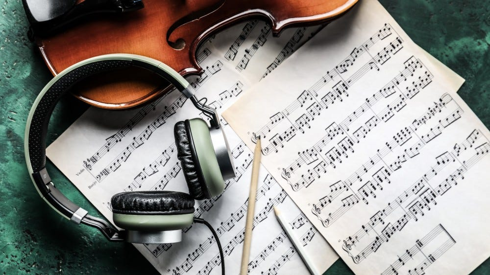 violin, headphones and notes on the table