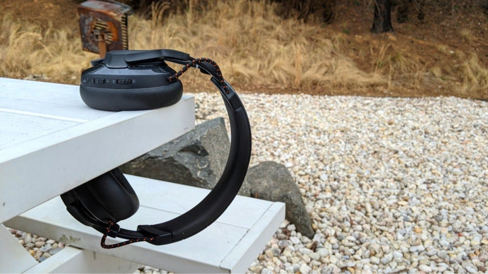 JBL Quantum 600 Headset resting on white table against natural backdrop.