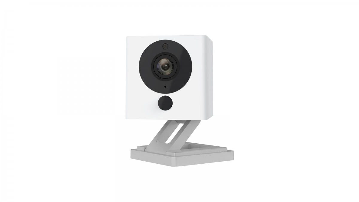 A white Wyze cam with black lens and grey stnnd.