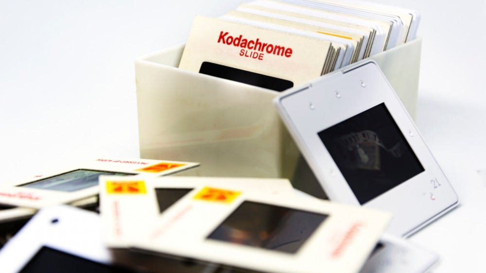 Group of 70's Kodachrome slides in a plastic box and scattered on a table