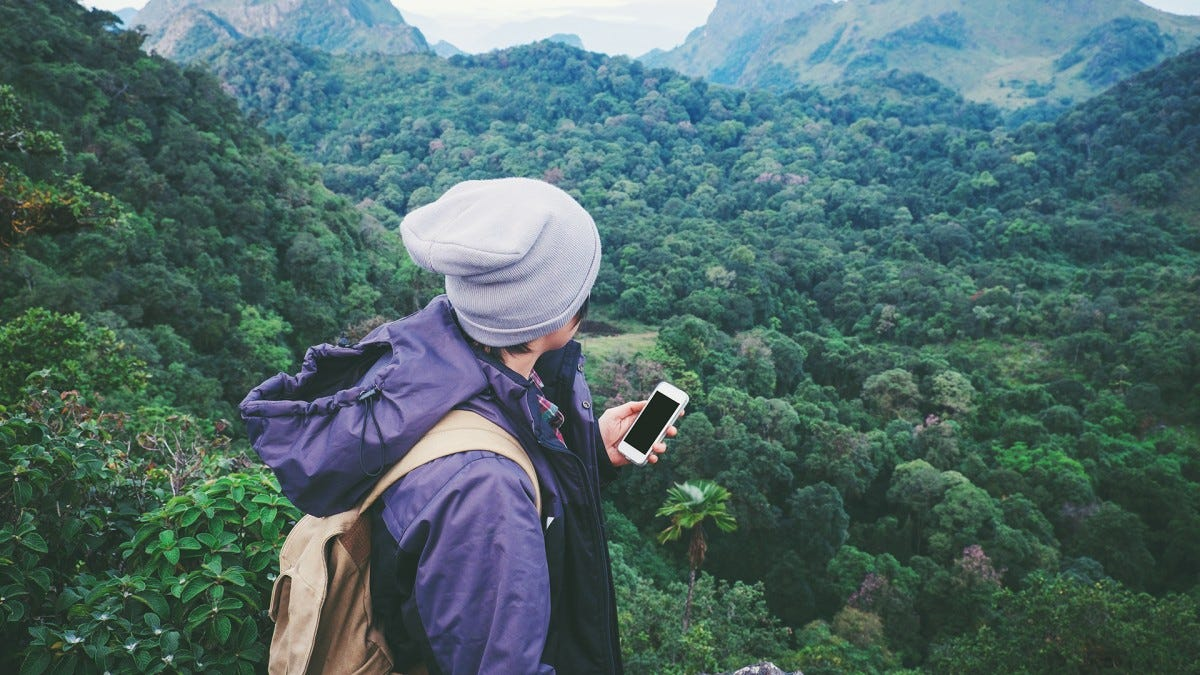 A hiker uses their phone to navigate outdoors.