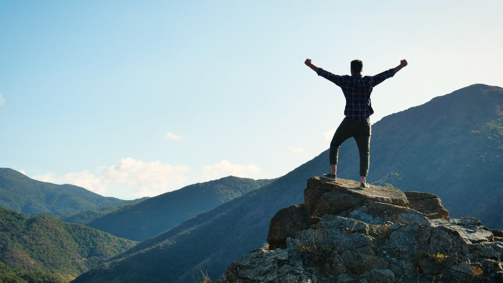 A photo of somone on a mountain, arms wide open, looking into the sunshine. They feel free.