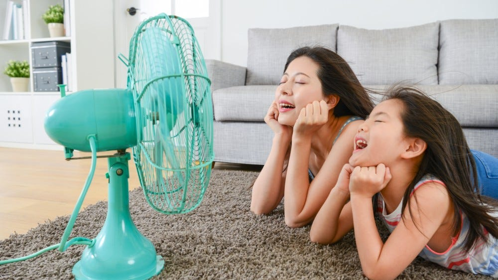 nice mother with young daughter lying in the living room and facing an electric fan enjoying blowing cool breeze together during the summer