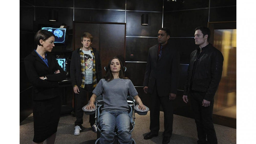 Dollhouse characters standing in a room around Eliza Dushku's character in a chair
