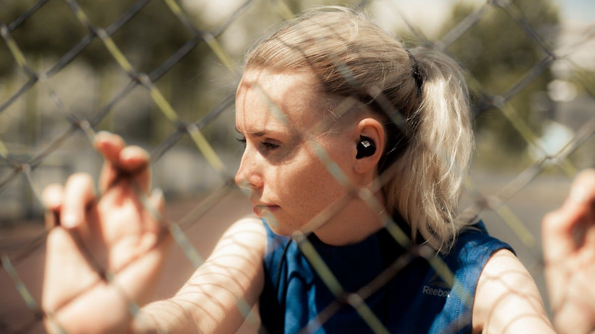 A woman leaning against a fence with a wireless earbud in her ear.