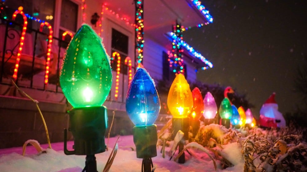 A row of Christmas lights lined up in front of a home.