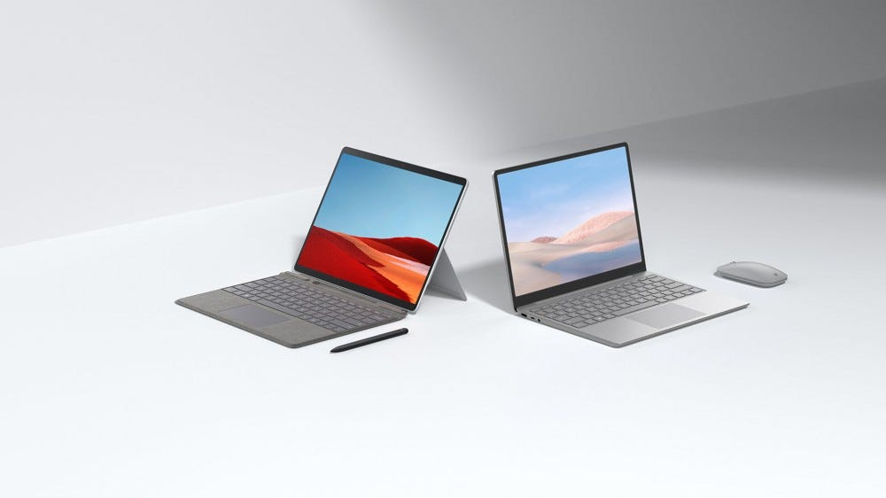 A Surface Pro X next to a Surface Laptop Go and mouse.