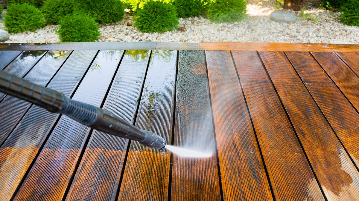 An attentive homeowner power washing their deck.