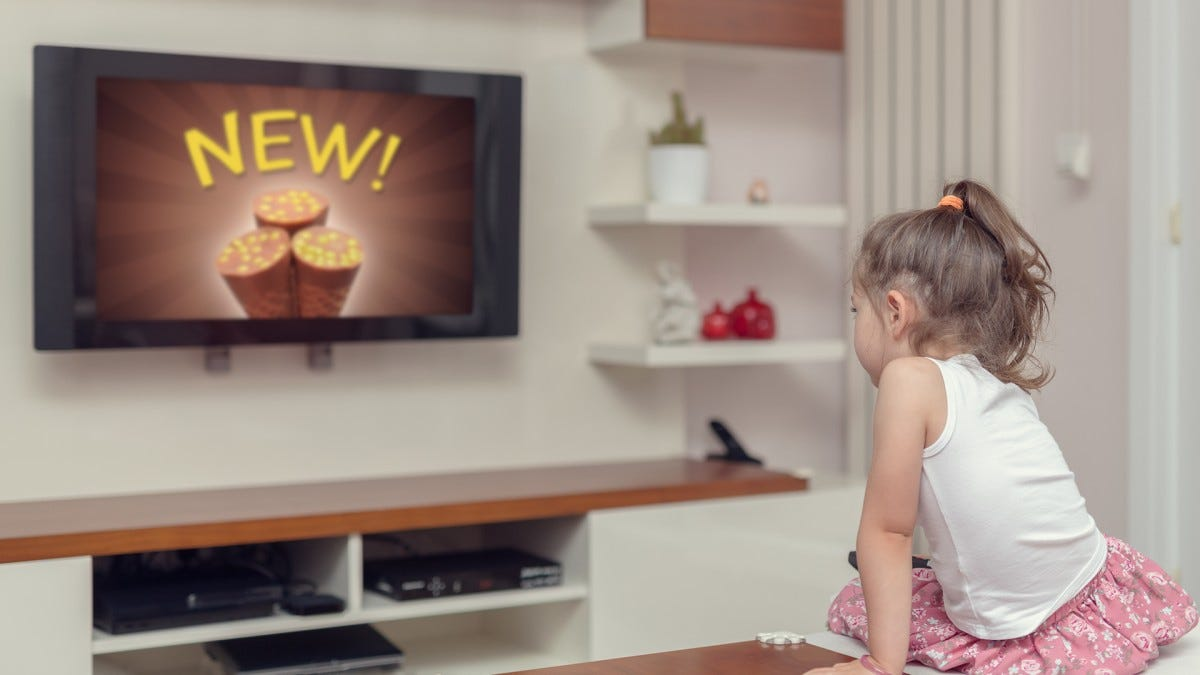 A child watches an ad on a TV.
