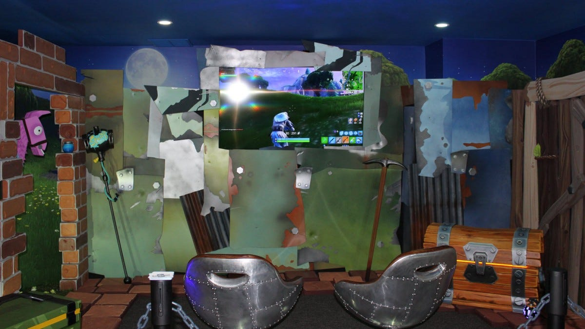 A game room featuring metal chairs, a treasure chest, and life-sized in-game items from Fortnite.