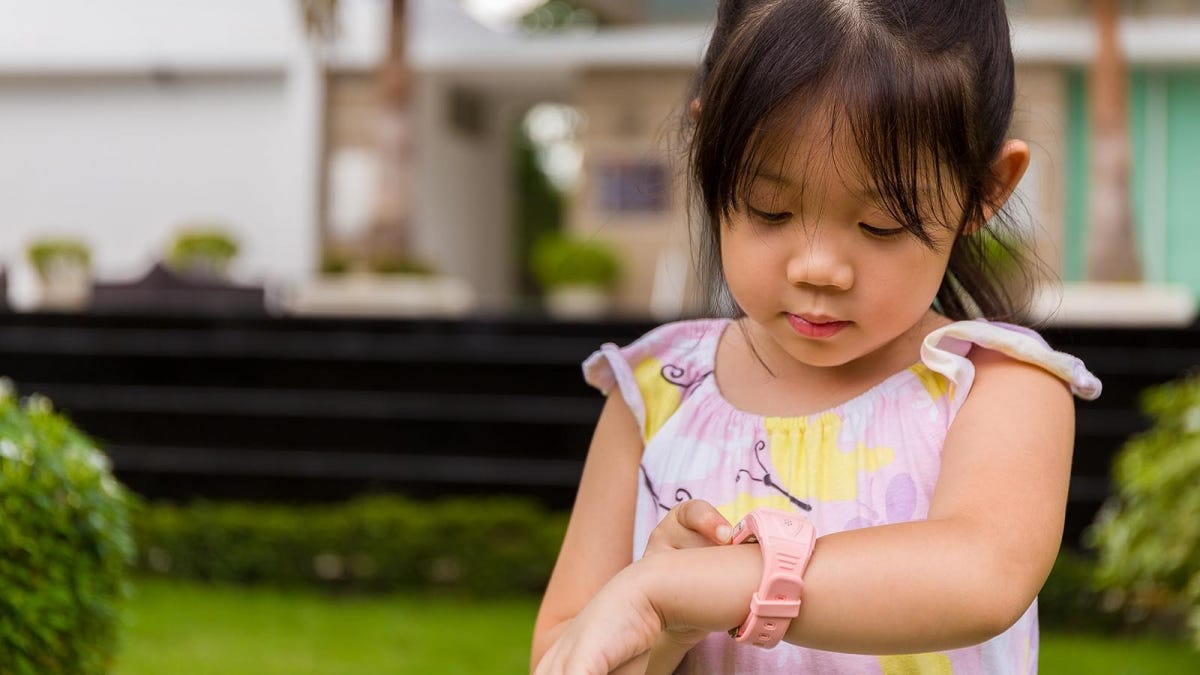 young girl, outside in a yard, looking at smart watch on her wrist