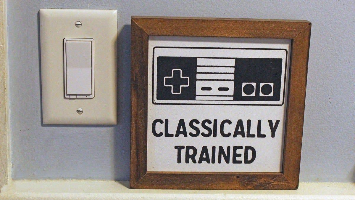 "A smart switch with a paddle-style toggle in a wall next to a sign that shows an NES controller and the words ""Classically trained."""