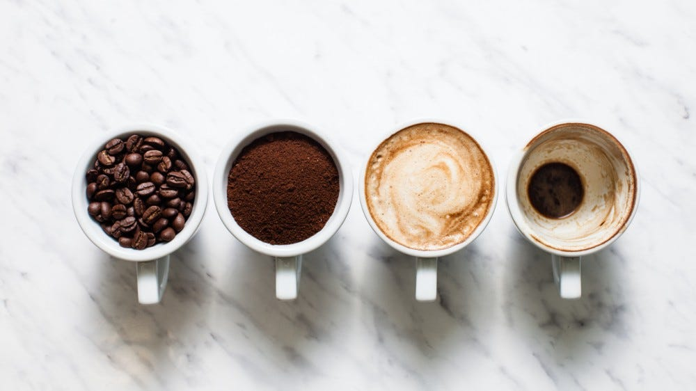 Four cups with coffee beans, grounds, made, and drank (in separate cups)