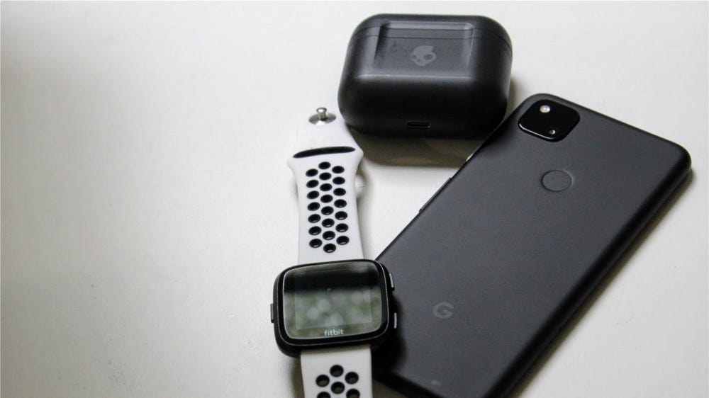 A Fitbit Versa, Skullcandy Indy Fuel, and Pixel 4a