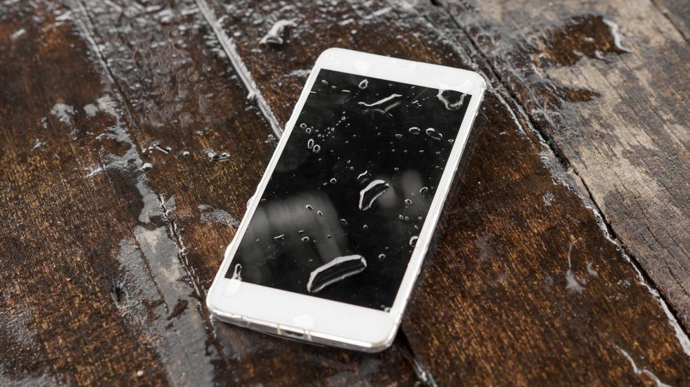 Wet smartphone on wood table