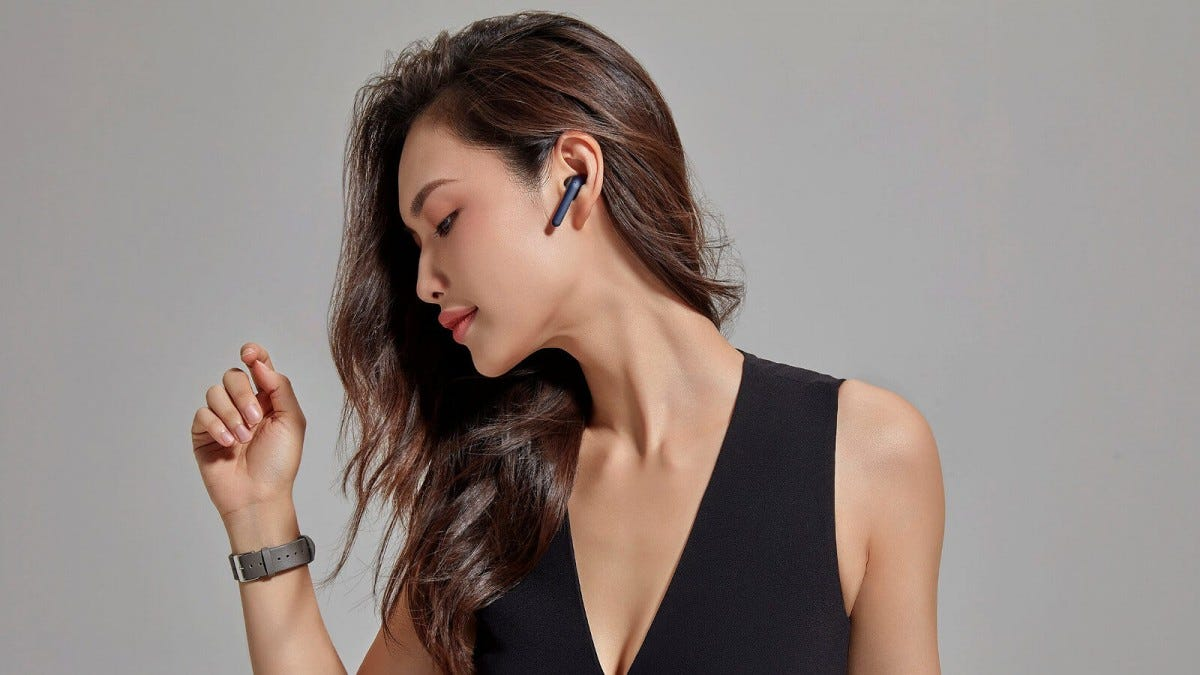 A young woman wearing a Mobvoi TicPods 2 True Wireless Earbud in her left ear.