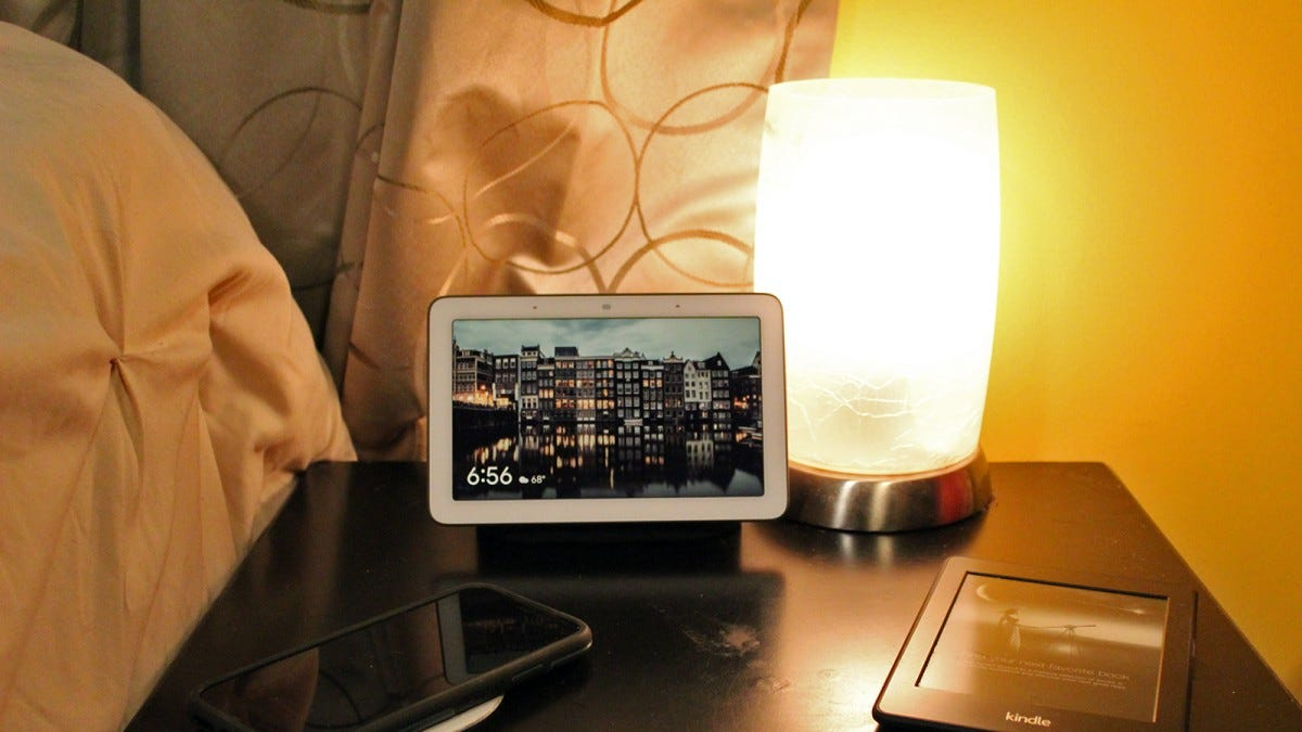 A Google Home Hub next to a smart lamp and phone charger.