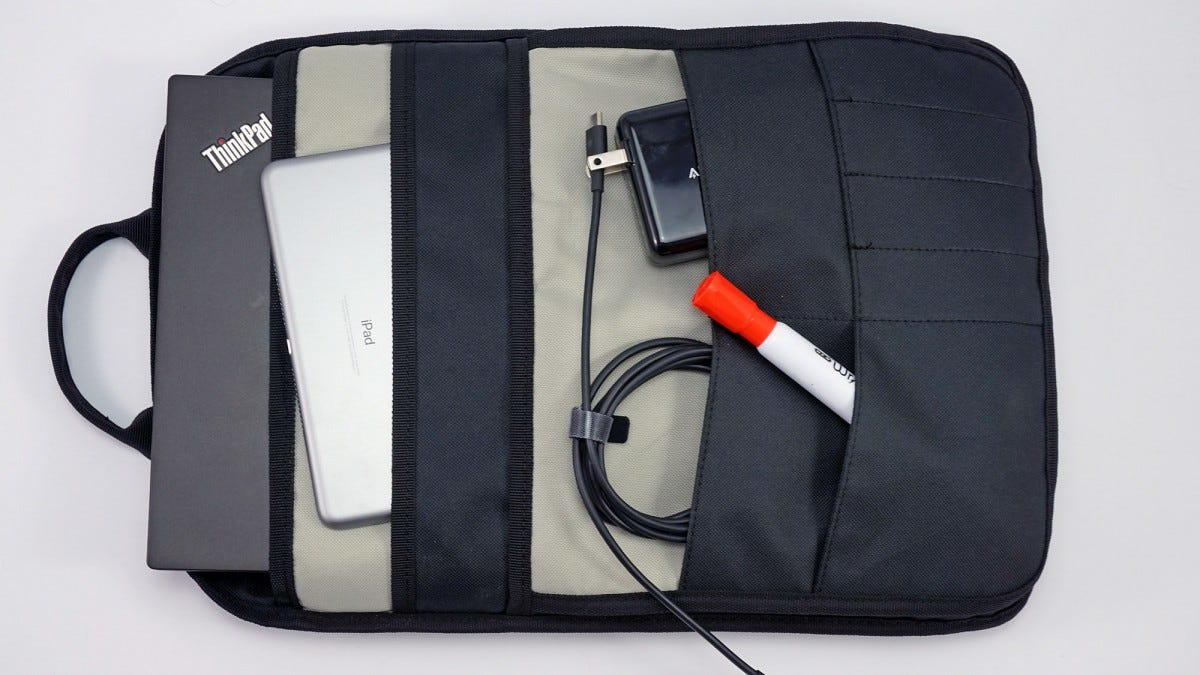 The organization sleeve from the Booē Hybrid 20 backpack, with 2 tablets, an outlet adapter, cord, and marker tucked into it.