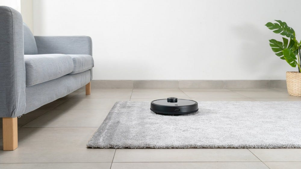 A Wyze robot vacuum cleaning a rug.